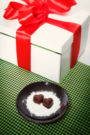 checked fabric: Two chocolate heart-shaped candies on a brown plate next to gift box with red ribbon against green checked fabric background, top view