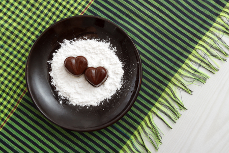 checked fabric: Two chocolate heart-shaped candies on a brown plate with sugar powder against green checked fabric background, horizontal top view