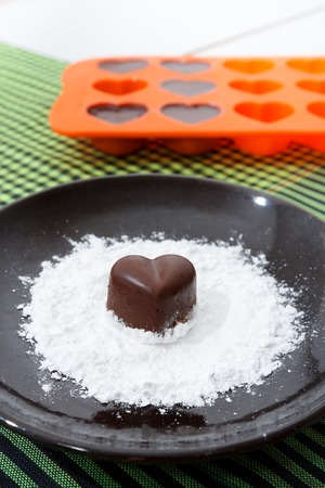 checked fabric: Chocolate heart-shaped candy on a brown plate with sugar powder and a bakin form with chocolates against green checked fabric background Stock Photo