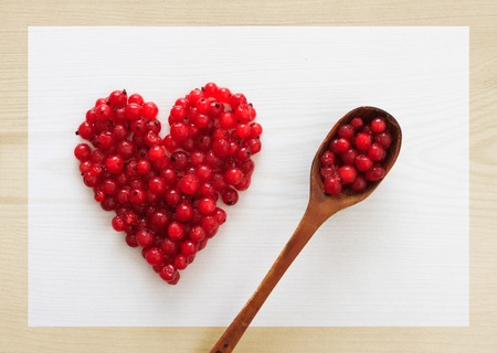 shape: Cranberries in heart shape and a spoon full of berries on wooden board, horizontal top view