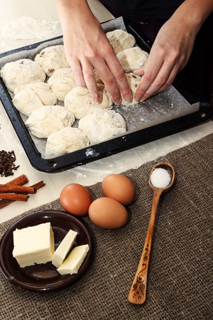 backing: Easter concept. Ingredients for cooking easter pie. Hands placing raw dough ready for coooking on backing pan