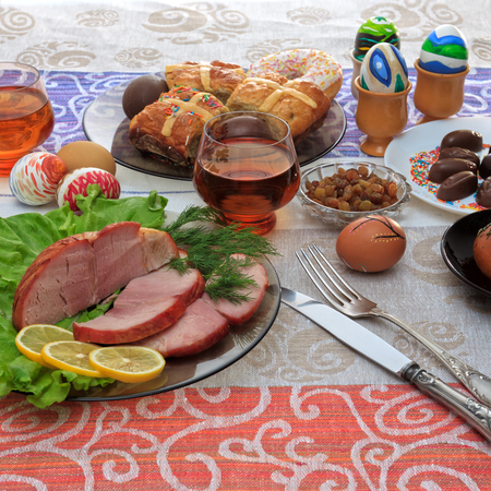 Traditional easter dinner set with sliced meat with lemon and herbs, bread, handmade colored eggs, chocolates, raisins, easter cake and glasses of juice on colorful tablecloth, close up view