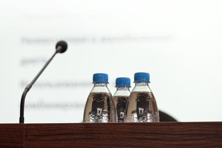 Seminar podium with blank screen, microphone and bottles of water on table ready for the speaker, selective focus, horizontal view