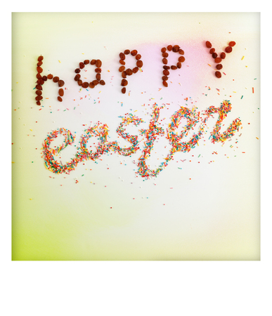 polaroid frame: Happy Easter phrase made from raisins and colorful baking sugar over colorful background with copy space and white polaroid frame, top view