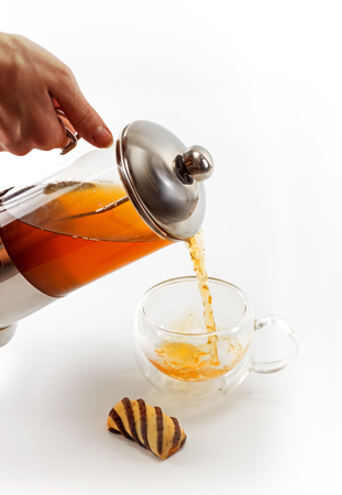 sided: Process of pouring tea from a teapot into a double sided glass with a cookie by side against white background, close up