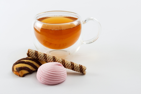 sided: Double sided wall glass cup full of green tea with sweets, biscuits and cinnamon next to it against white background, close up horizontal view