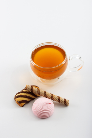 sided: Double sided wall glass cup full of green tea with sweets, biscuits and cinnamon next to it against white background, close up with copy space