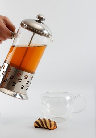 double glass: Process of pouring tea from a teapot into a double sided glass with a cookie by side against white background, close up