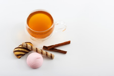 double glass: Double sided wall glass cup full of green tea with sweets, biscuits and cinnamon next to it against white background, close up horizontal view with copy space