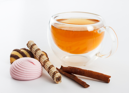 double glass: Double sided wall glass cup full of green tea with sweets, biscuits and cinnamon next to it against white background, close up horizontal view