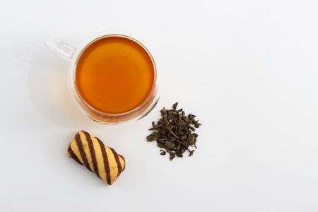 sided: Double sided wall glass cup full of green tea with sweets, biscuits and pile of dried leaves next to it against white background, close up horizontal top view with cop Stock Photo