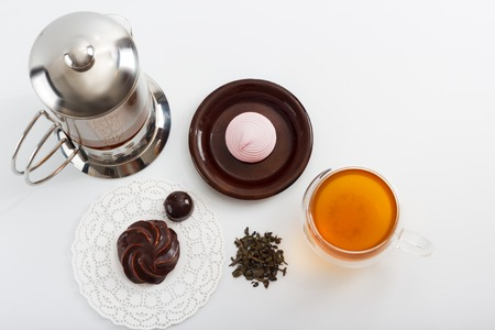 sided: Glass tea pot with double sided wall glass cup full of green tea with sweets and biscuits on brown plate next to it against white background, close up horizontal top view