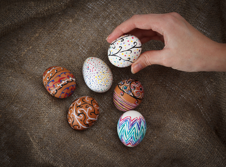 chose: Colorful Easter eggs on burlap, female hand chose and pick one, horizontal top view close up Stock Photo