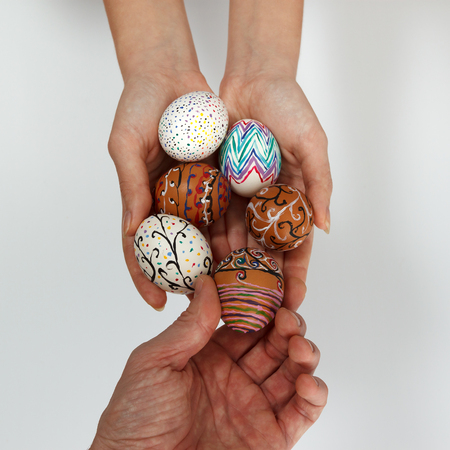 chose: Colorful Easter eggs in female hands, male hand chose and pick one egg against white background, horizontal top view close up