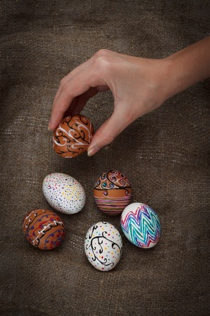 chose: Colorful Easter eggs on burlap, female hand chose and pick one, top view close up Stock Photo