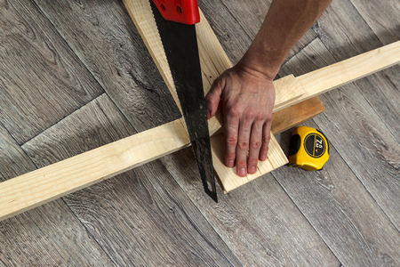 furniture hardware: Home improvement process, saw, timber and ruler on wooden floor, horizontal top view