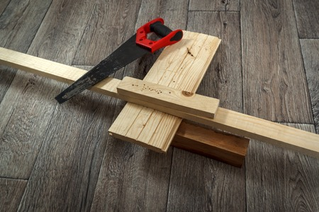 furniture hardware: Home improvement process, saw and timber on wooden floor, horizontal view