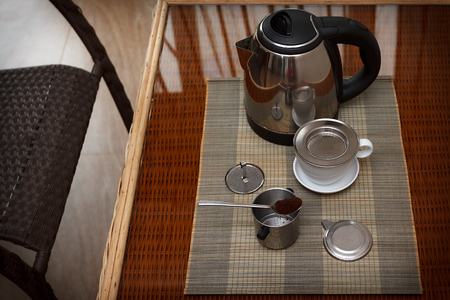 coffee filter: Morning coffee served in vietnam coffee filter on rattan table with two rattan chairs, natural light photo, closeup horizontal view