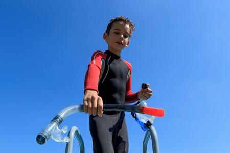 Ein Junge bereit zum Tauchen in Taucheranzug legt auf der Tauchermaske, Portrait gegen den blauen Himmel an einem sonnigen Tag