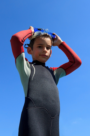 sky diving: Young boy ready for diving in diving suit puts on diving mask, portrait against blue sky on sunny day