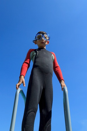 sea  scuba diving: Young boy ready for diving in diving suit puts on diving mask, portrait against blue sky on sunny day