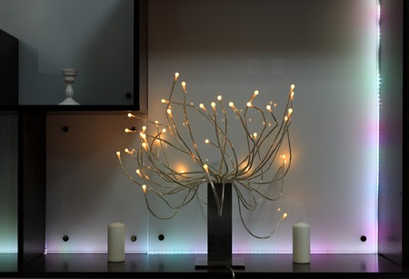 candes: Shelf with lighting decoration, led lamps tree and candes on black shelves against multicolor backlit plastic panel Stock Photo