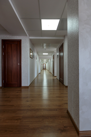 wooden floors: modern generic long office hallway with wooden floors and white painted walls