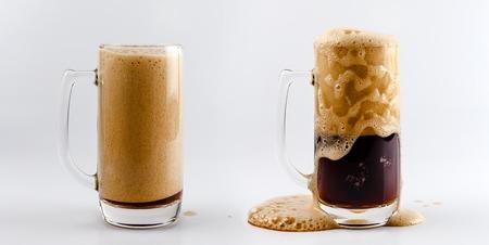 cerveza negra: Conjunto de dos tazas de vidrio de cerveza. proceso de cerveza valiente oscura que vierte en una taza de cristal de cerveza, salpicaduras, gotas y espuma alrededor de la taza de cristal contra el fondo blanco Foto de archivo