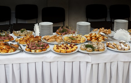 Catering banquet table with baked food snacks, sandwiches, cakes, cups and plates, self serve, open buffet dinner, horizontal view