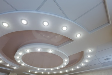 Modern layered ceiling with embedded lights and stretched ceiling inlay, light turned on