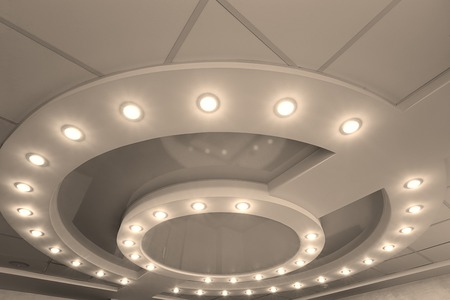 inlay: Modern layered ceiling with embedded lights and stretched ceiling inlay, lights on Stock Photo