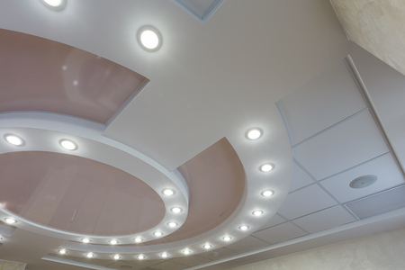 Modern layered ceiling with embedded lights and stretched ceiling inlay, lights on Stock Photo