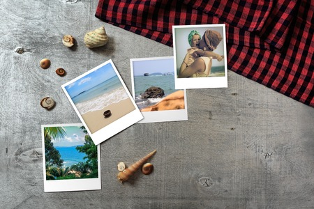 snapshots: Beautiful seaside snapshots arranged on rustic wooden background with seashells and a scarf around, horizontal top view with copy space