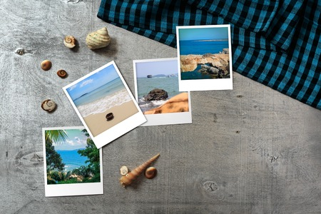 Beautiful seaside snapshots arranged on rustic wooden background with seashells and a scarf around, horizontal top view with copy space