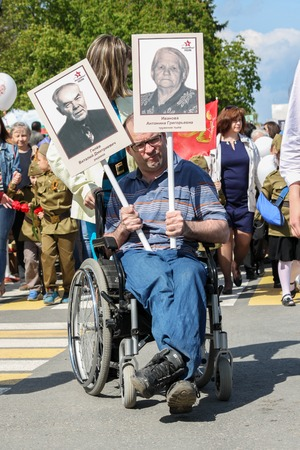 disabled person: ULYANOVSK, RUSSIA - MAY 9, 2016: A disabled person in wheelchair holds portraits of relatives in the Immortal regiment on 9 May, 2016 in Ulyanovsk, Russia
