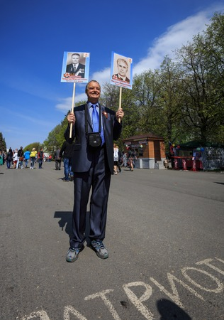 annexation: ULYANOVSK, RUSSIA - MAY 9, 2016: A man with portraits of relatives takes part in the Immortal regiment on 9 May, 2016 in Ulyanovsk, Russia