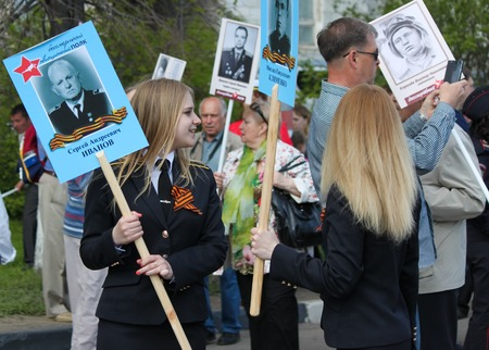 ULYANOVSK, RUSSIA - MAY 9, 2016: Two female pilot cadets hold portraits of pilot relatives in the Immortal regiment on 9 May, 2016 in Ulyanovsk, Russia