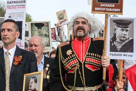 cossack parade: ULYANOVSK, RUSSIA - MAY 9, 2016: Man in Cossack military uniform holds portrait of relatives at Immortal regiment on 9 May, 2016 in Ulyanovsk, Russia Editorial