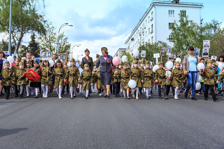 annexation: ULYANOVSK, RUSSIA - MAY 9, 2016: Children in uniform hold portraits of relatives in the Immortal regiment on 9 May, 2016 in Ulyanovsk, Russia Editorial