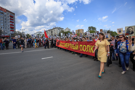 immortal: ULYANOVSK, RUSSIA - MAY 9, 2016: People hold red banner of Immortal regiment and portraits of their relatives on 9 May, 2016 in Ulyanovsk, Russia