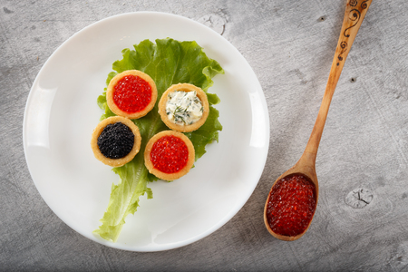 full filled: Tartlets filled with black caviar and cheese and dill salad on white plate and leaf against rustic wooden background with a wooden spoon full of caviar, horizontal top view Stock Photo