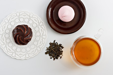 sided: Double sided wall glass cup full of green tea with sweets, biscuits and pile of dried leaves next to it against white background, close up horizontal top view