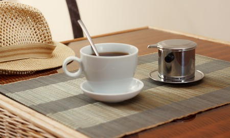 coffee filter: Morning coffee served in vietnam coffee filter on rattan table, natural light photo, closeup horizontal view