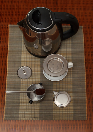 coffee filter: Morning coffee served in vietnam coffee filter on rattan table with two rattan chairs, natural light photo, closeup view