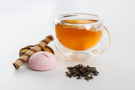 sided: Double sided wall glass cup full of green tea with sweets, biscuits and pile of dried leaves next to it against white background, close up horizontal view