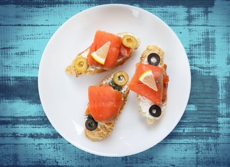 king salmon: Tasty various italian sandwiches with seafood against rustic wooden background. Crostini with cheese, red fish fillet, lemon and sliced olives, horizontal top view