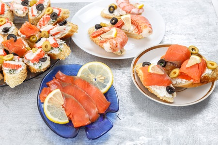 king salmon: Tasty various sandwiches with seafood against rustic wooden background. Crostini with cheese, shrimps, mussels, red fish, crab sticks, lemon, olives on plates, close up with selective focus