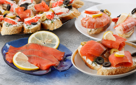 king salmon: Tasty various italian sandwiches with seafood against rustic wooden background. Crostini with cheese, shrimps, mussels, red fish, crab sticks, lemon, sliced olives on different plates, close up with selective focus Stock Photo