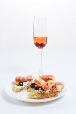king salmon: Tasty various italian sandwiches with seafood against white background. Crostini with cheese, shrimps and olives on white plate, glass of wine, close up with selective focus