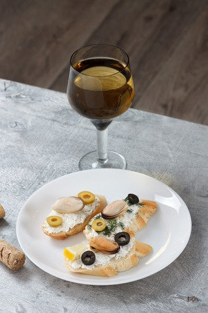 king salmon: Tasty various italian sandwiches with seafood against rustic wooden background. Crostini with cheese, mussels and olives on white plate and wine, close up with selective focus